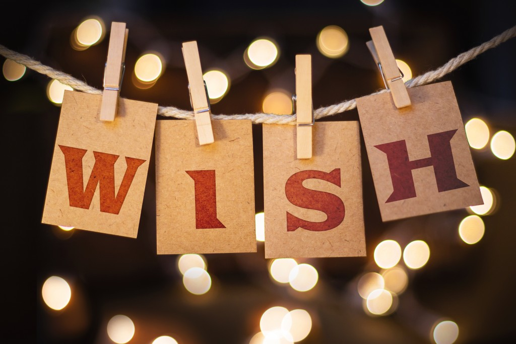 The word WISH printed on clothespin clipped cards in front of defocused glowing lights.