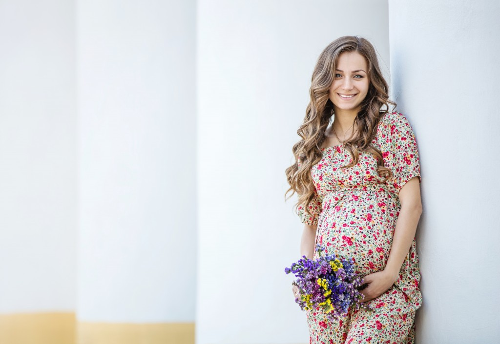 Pretty pregnant woman with a bunch of flowers near the column