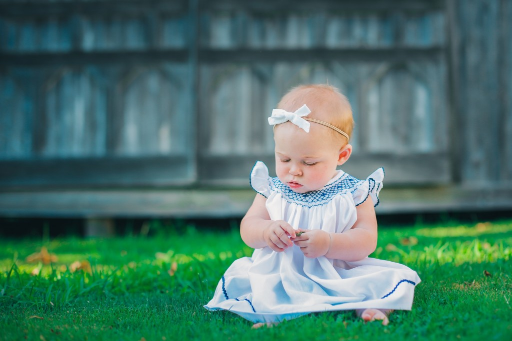 infant baby girl in dress sitting green grass playing with grass by barn