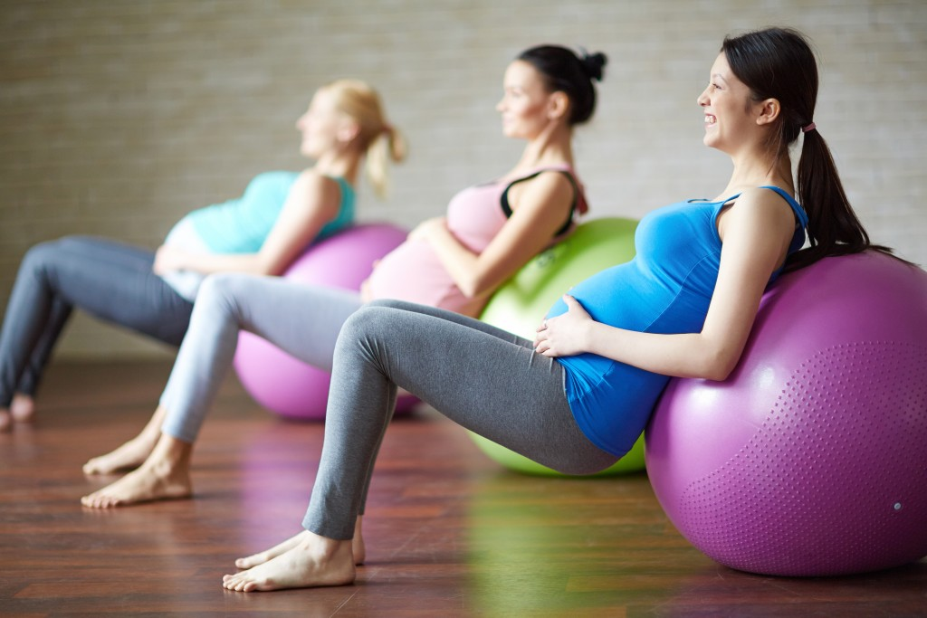 Several pregnant women exercising with ball in gym